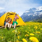 Group of kids, boys and girls sitting together in the tent in dandelion field